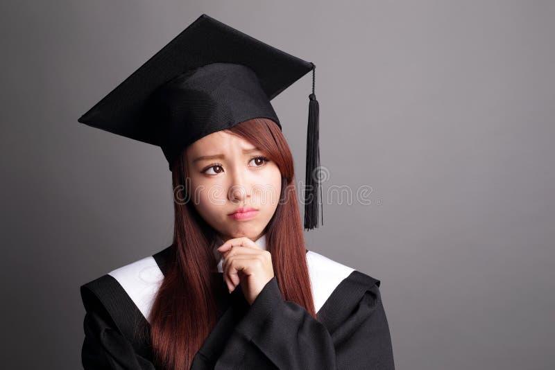 A mulher do aluno diplomado pensa foto de stock