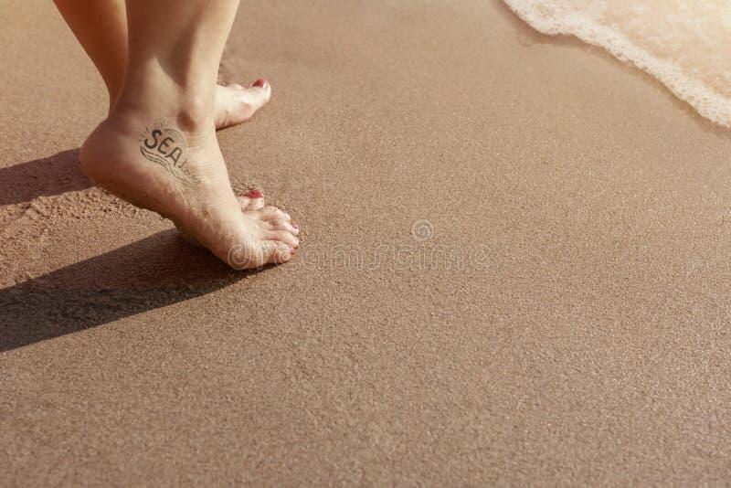 Mulher do amante do mar com tatuagem que anda na praia da areia durante o por do sol imagem de stock royalty free