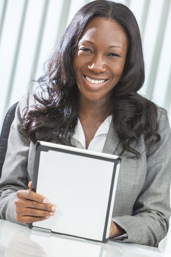 Mulher do americano africano que usa o computador da tabuleta foto de stock