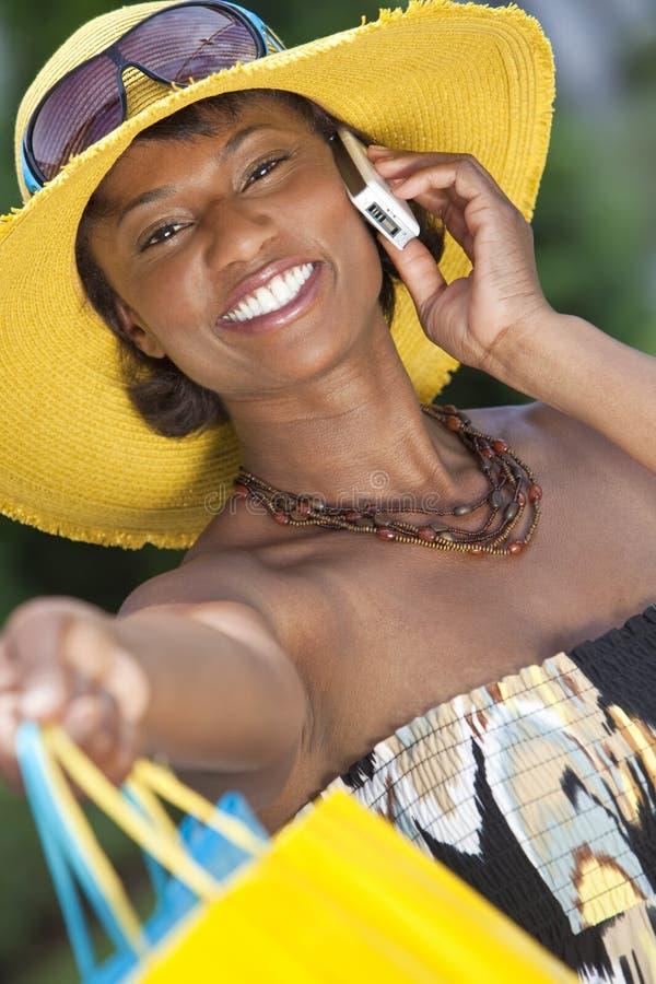 Mulher do americano africano, sacos de compra & telefone de pilha imagem de stock