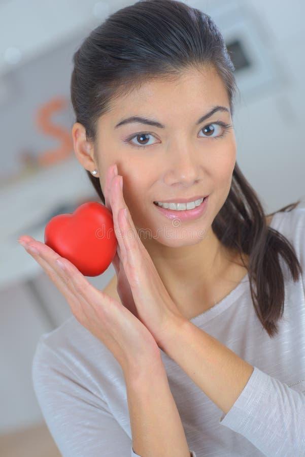 Mulher do amor que sorri guardando o coração vermelho fotografia de stock