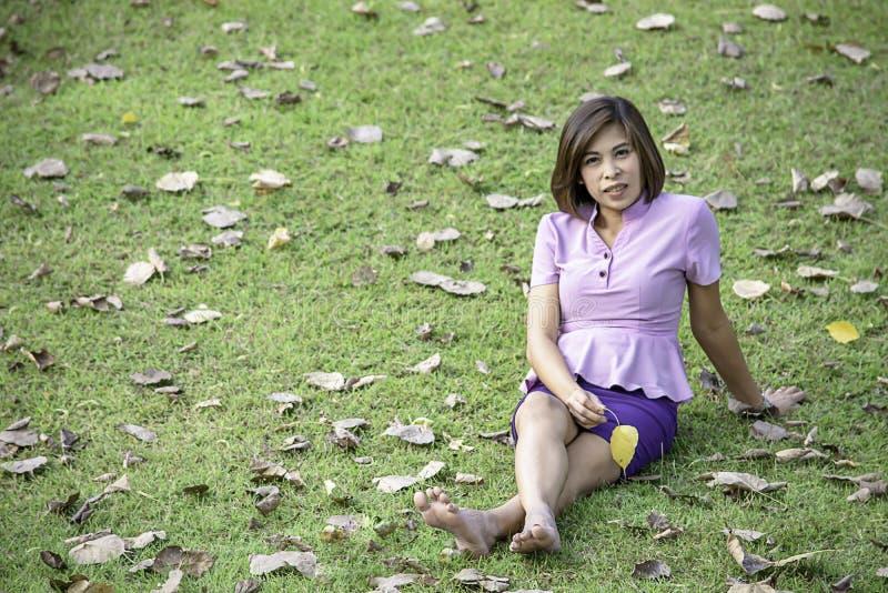 Mulher do Asean do retrato que senta-se no gramado em um parque fotos de stock