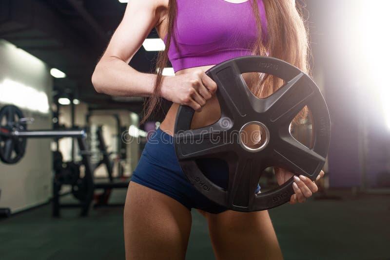 Mulher do atleta que dá certo com barbell Menina da aptidão do biquini no sportswear que faz o exercício no gym imagem de stock