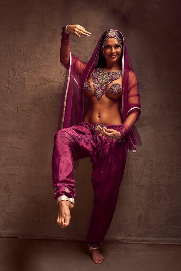 mulher do Barriga-dançarino em calças, no purdah e na ornamentação afghani imagem de stock