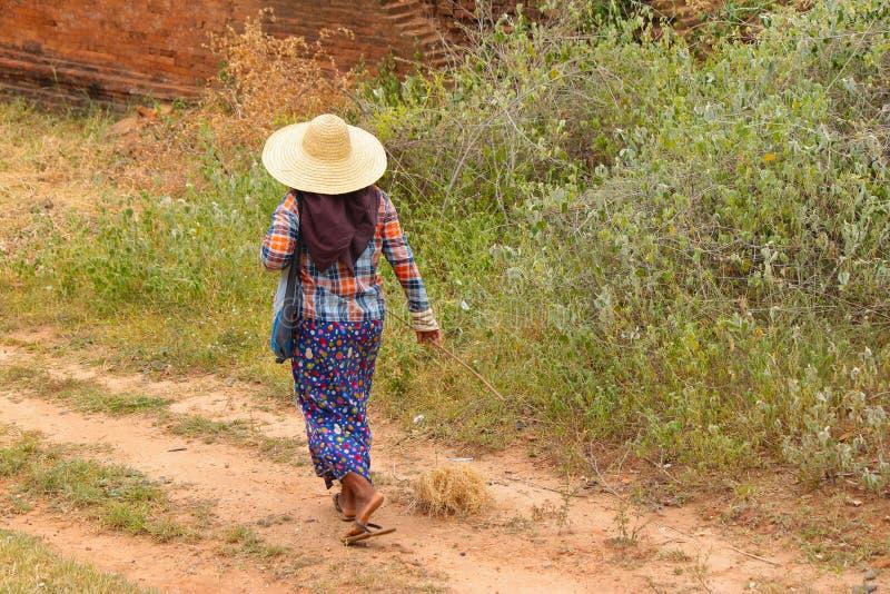 Mulher do birmanês que anda com os pés descalços com sua roupa típica e colorida em Bagan, Myanmar Burma imagens de stock royalty free