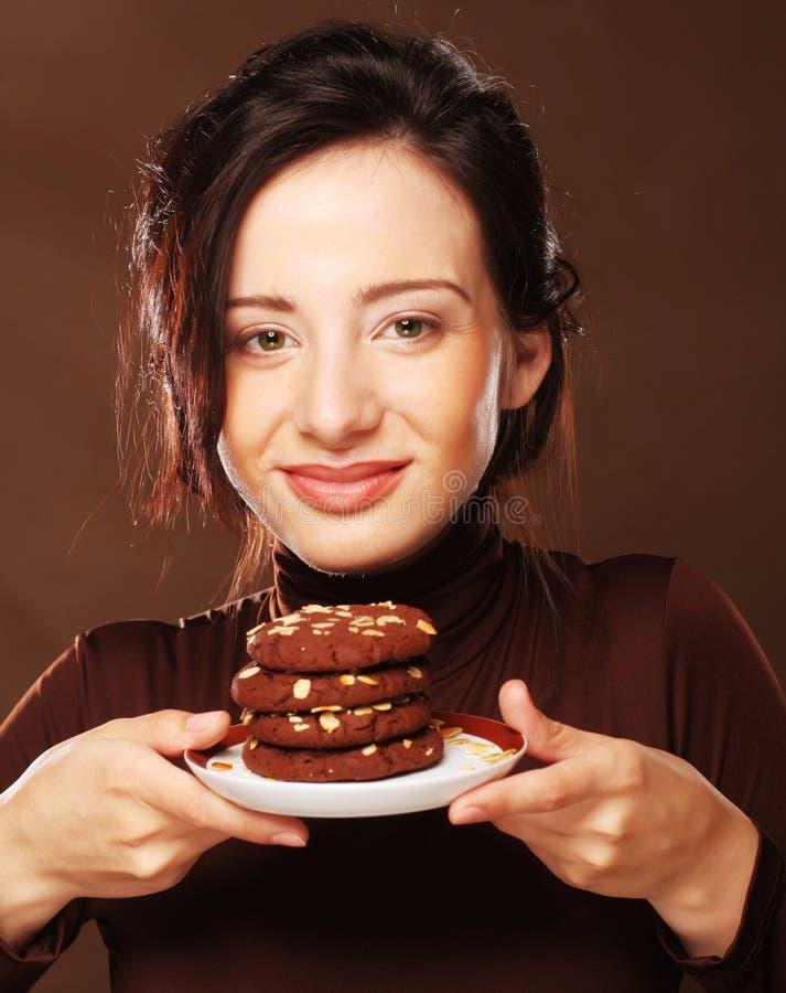 Mulher do biscoito que come biscoitos dos peda?os de chocolate no fundo bege fotografia de stock royalty free