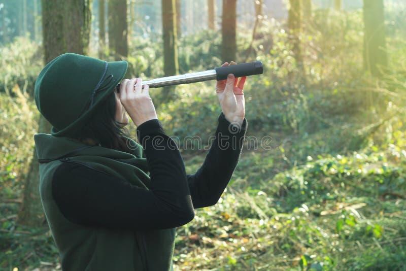 Mulher do caçador com telescópio pequeno em uma floresta fotos de stock