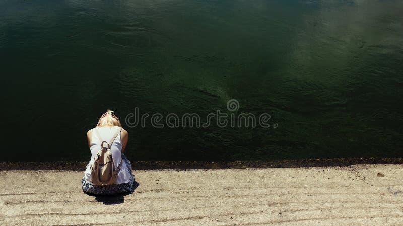 Mulher do cabelo louro que senta-se pela água do rio escura, triste fotos de stock royalty free