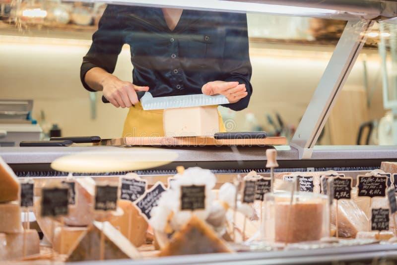 Mulher do caixeiro de loja que classifica o queijo na exposição do supermercado foto de stock royalty free