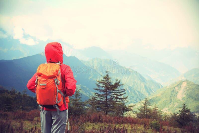 Mulher do caminhante no pico de montanha fotos de stock