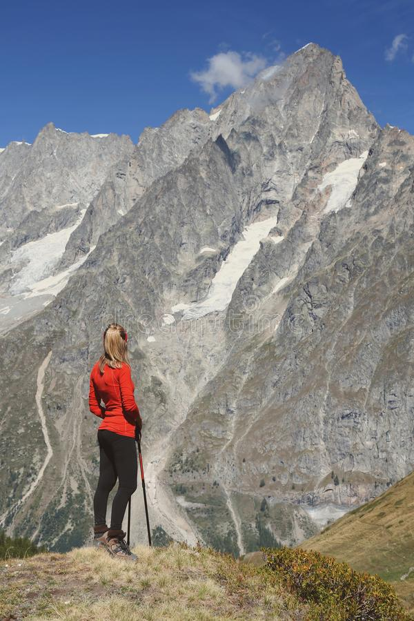 Mulher do caminhante que olha a montanha imagem de stock