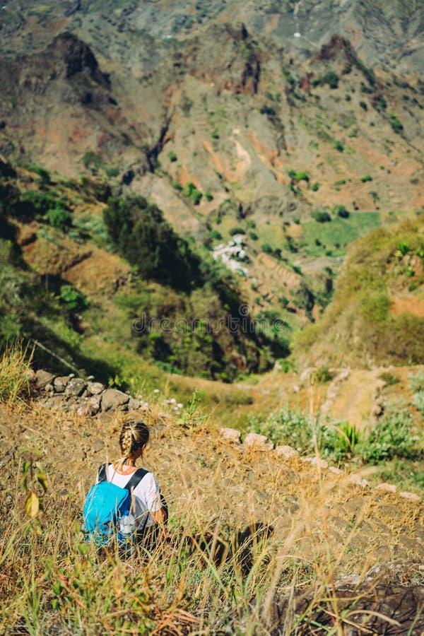 A mulher do caminhante toma um resto na inclinação de montanha Sentar-se na cimeira afiada e aprecia a vista espetacular Paisagem fotografia de stock royalty free