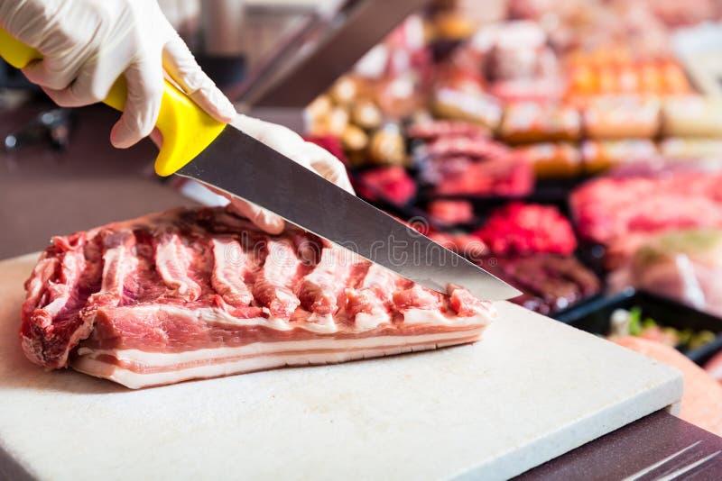 Mulher do carniceiro que corta a parte de carne do reforço em sua loja imagens de stock royalty free