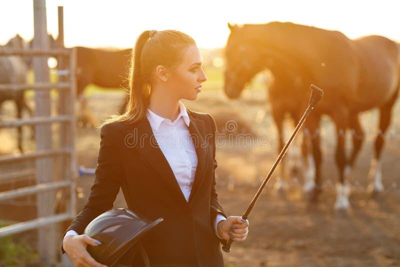 Mulher do cavaleiro com o chicote no por do sol imagens de stock royalty free