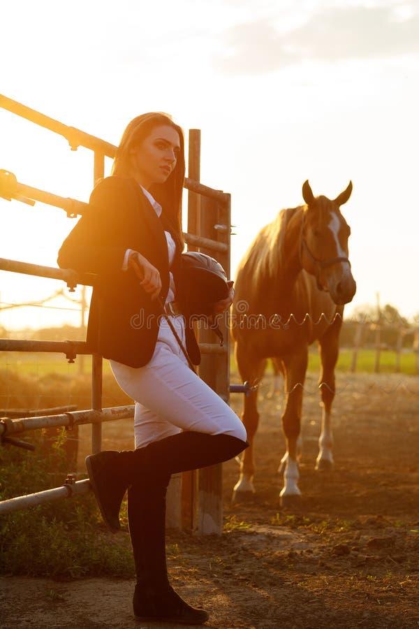 Mulher do cavaleiro com o chicote no por do sol fotos de stock royalty free
