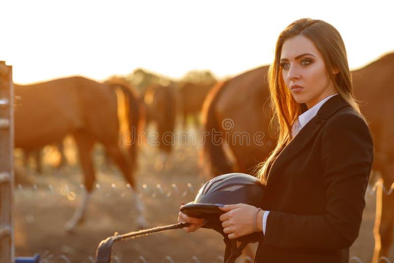 Mulher do cavaleiro com o chicote no por do sol foto de stock