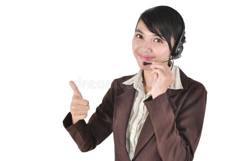 Mulher do centro de chamadas com os auriculares que mostram o polegar acima fotografia de stock
