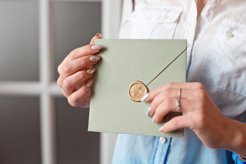 Mulher do close-up com o corpo magro que realiza nas mãos o cartão cinzento-verde do envelope da forma do quadrado da cor do cart foto de stock