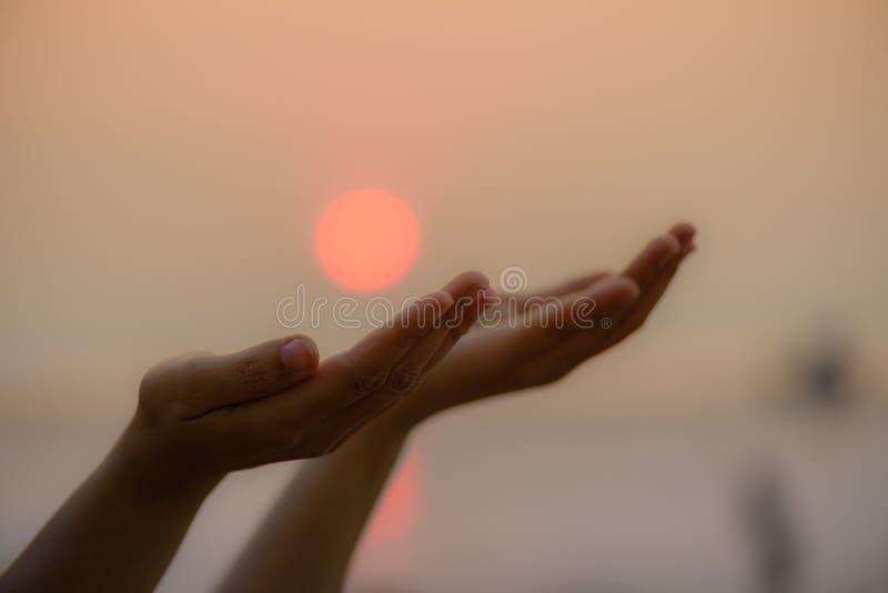 A mulher do close up entrega rezar para abençoar do deus durante o por do sol fotos de stock royalty free