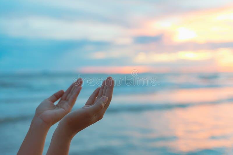 A mulher do close up entrega rezar para abençoar do deus durante o por do sol imagens de stock royalty free