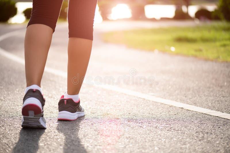 Mulher do close up que anda para no lado da estrada Etapa, caminhada e conceito exterior das atividades do exercício foto de stock