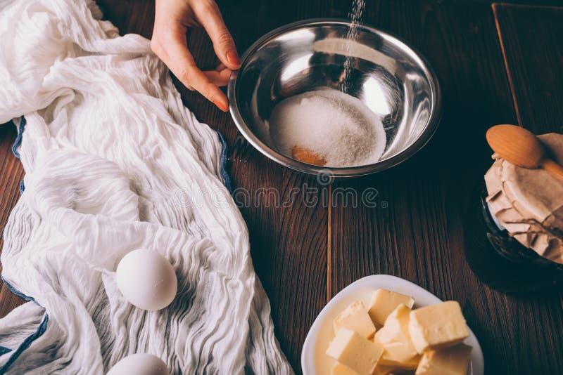 Mulher do close-up que cozinha a massa para o açúcar de derramamento da torta foto de stock