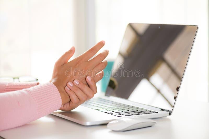 Mulher do close up que guarda sua dor do pulso de usar o computador escritório imagens de stock