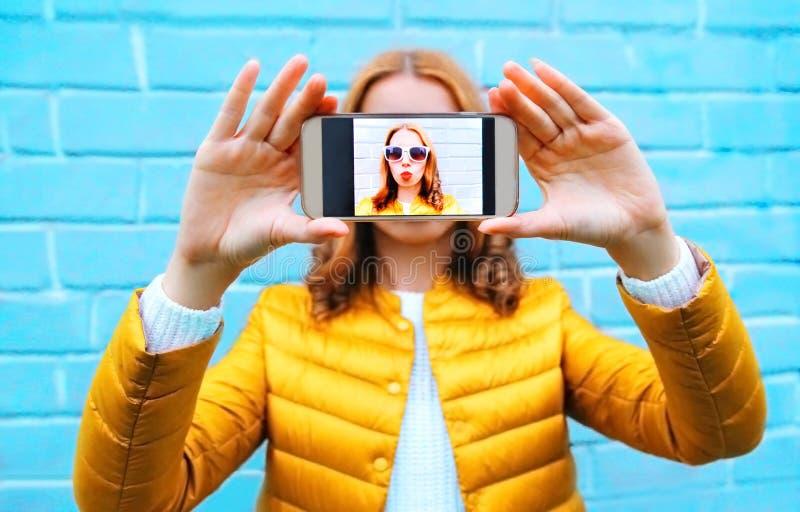 A mulher do close up toma o autorretrato da imagem no smartphone no azul fotografia de stock royalty free