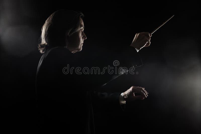 Mulher do condutor da música que conduz a orquestra imagens de stock