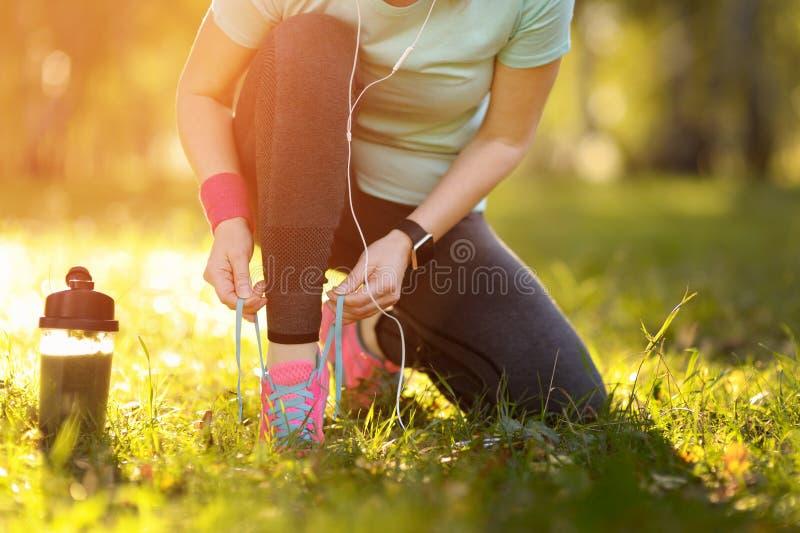 Mulher do corredor do esporte que amarra laços antes de treinar Maratona fotografia de stock royalty free