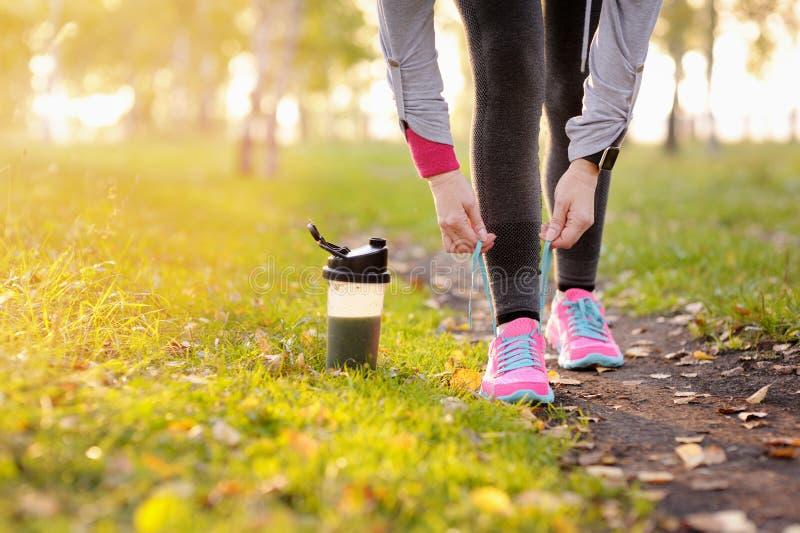 Mulher do corredor do esporte que amarra laços antes de treinar Maratona foto de stock royalty free