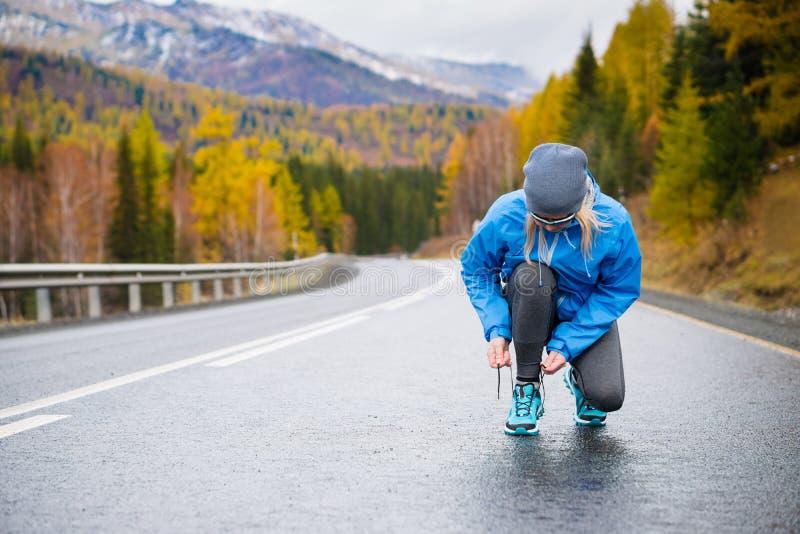 Mulher do corredor do esporte que amarra laços antes de treinar Maratona fotos de stock