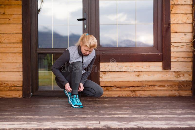 Mulher do corredor do esporte que amarra laços antes de treinar Maratona imagem de stock royalty free