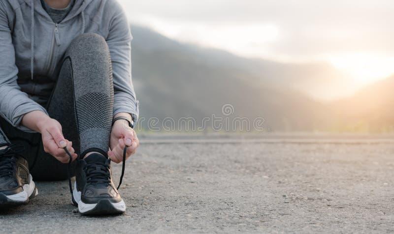 Mulher do corredor do esporte que amarra la?os antes de treinar Maratona foto de stock