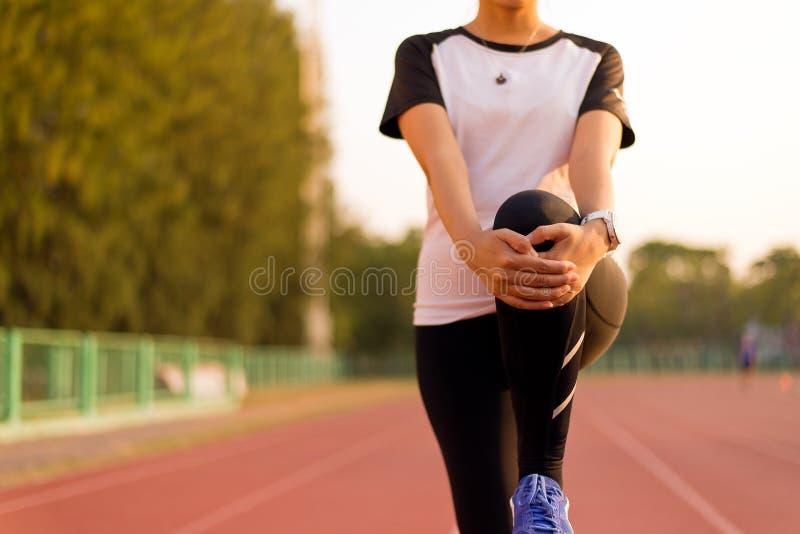 Mulher do corredor do esporte que estica para aquecer-se antes de correr exercícios e o treinamento fazendo do exercício imagem de stock royalty free
