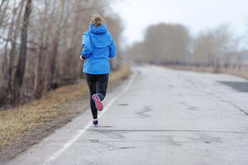 Mulher do corredor que corre na estrada na natureza bonita Traini movimentando-se foto de stock royalty free