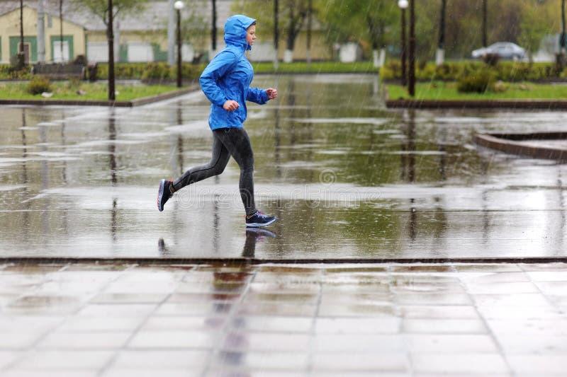 Mulher do corredor que corre no parque na chuva Treinamento movimentando-se para m fotografia de stock royalty free