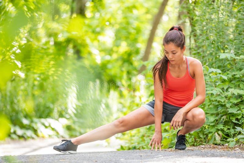 Mulher do corredor que estica a menina de corrida da corrida do exercício do pé que faz os estiramentos dos pés exteriores no par imagem de stock