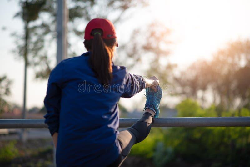 Mulher do corredor que estica o músculo do pé que prepara-se no parque verde no por do sol após o exercício fotos de stock royalty free