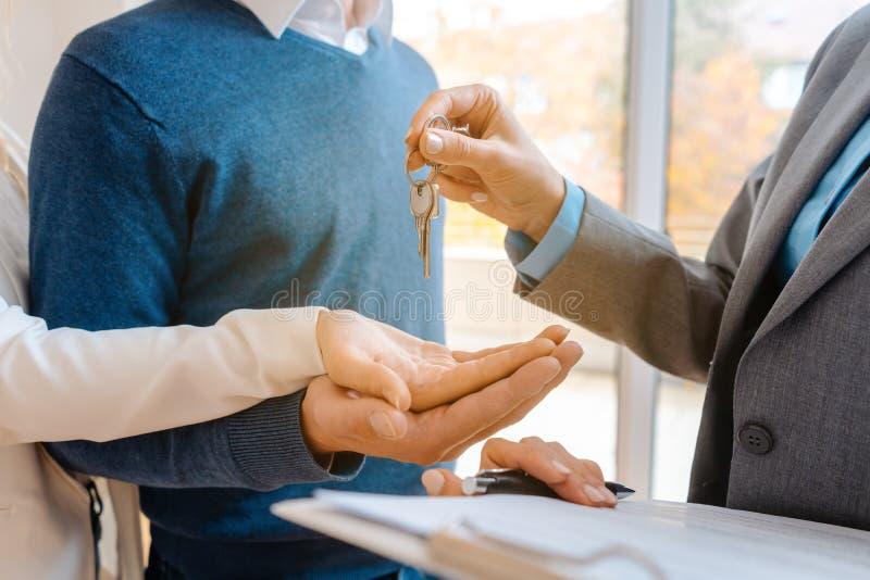Mulher do corretor de imóveis que dá chaves da casa para acoplar-se, close up imagens de stock
