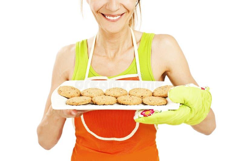 Mulher do cozimento que mostra cookies na bandeja fotos de stock royalty free