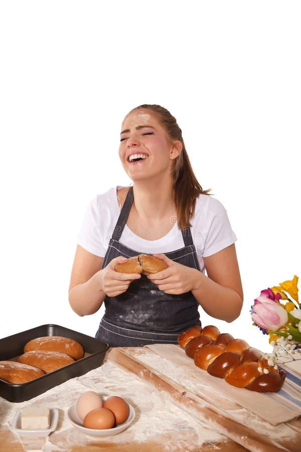 Mulher do cozimento que ri durante a tentativa do naco fresco do centeio imagem de stock royalty free