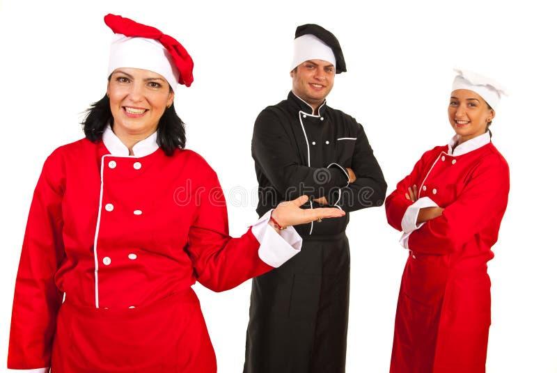 Mulher do cozinheiro chefe que apresenta sua equipe imagens de stock royalty free