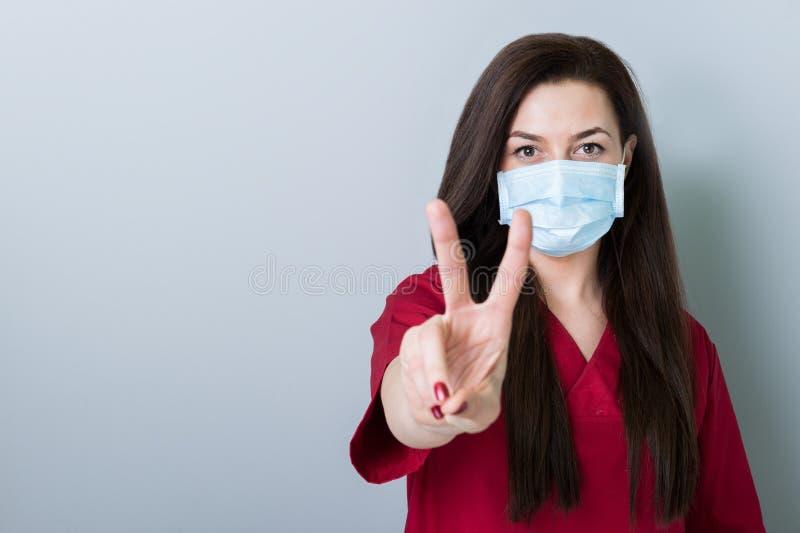 Mulher do dentista que mostra o gesto da paz no espaço cinzento da cópia foto de stock