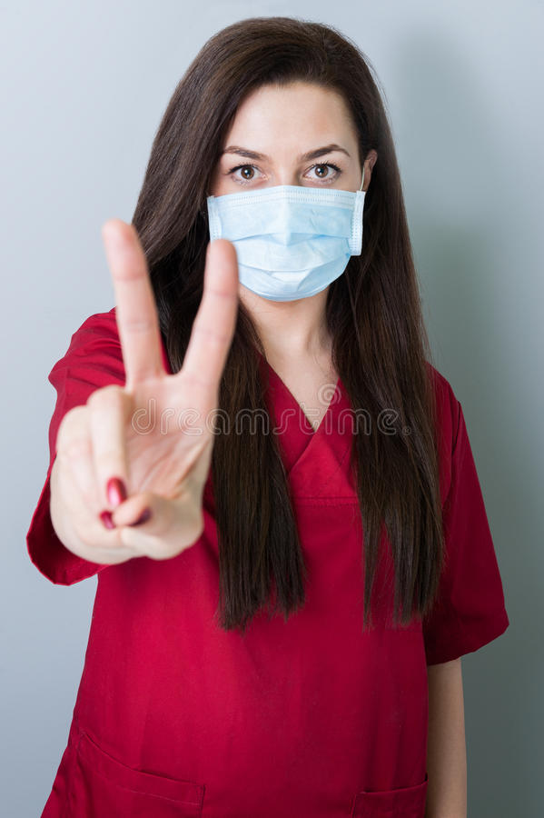 Mulher do dentista que mostra o sinal da paz ou da vitória imagens de stock