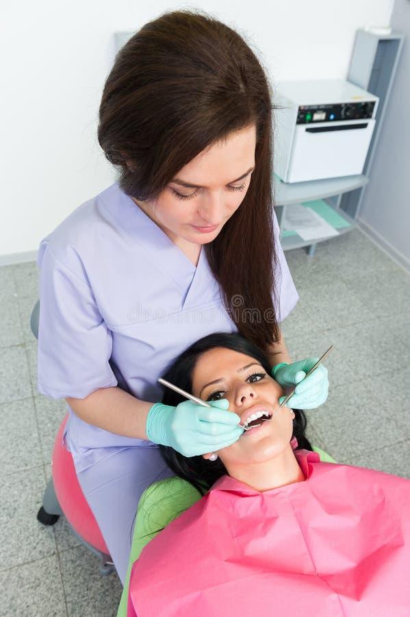 Mulher do dentista que trabalha com paciente bonito imagens de stock royalty free