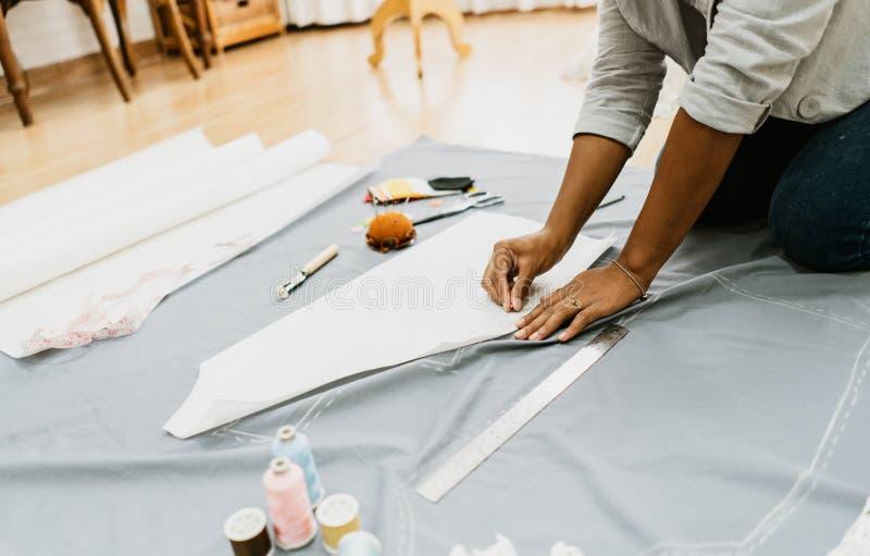Mulher do desenhador de moda que trabalha em sua loja do alfaiate, costurando, fim acima Alfaiate Made e conceito pequeno do prop imagens de stock royalty free