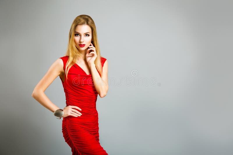 Mulher do encanto no vestido vermelho em Gray Background foto de stock