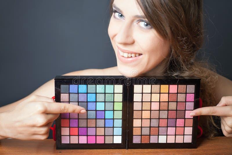 Mulher do encanto que aponta na paleta colorida para a composição da forma fotografia de stock royalty free