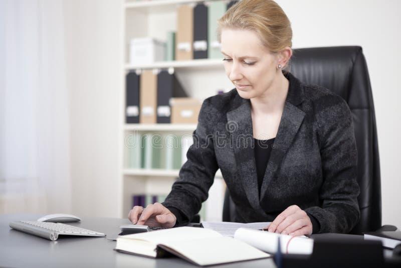 Mulher do escritório que senta-se em suas vendas calculadoras da mesa imagem de stock